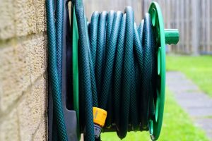 green garden hose wrapped up on a wall spindle