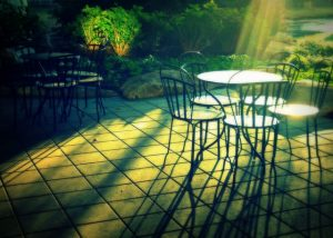 Table and chairs on a backyard patio at sunset.