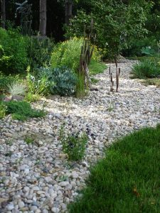 dry creek bed along side the edge of a back yard